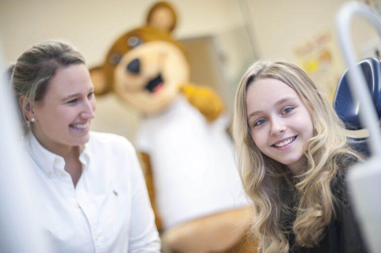 lächelnde Mitarbeiterin mit zufriedener Kids Club Patientin