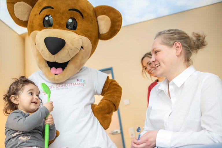 zwei Mitarbeiterinnen, Maskottchen Tommy und eine junge Patientin