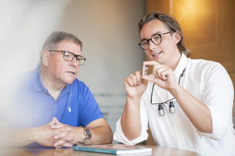 Dr. Schlotmann erklärt einem Patienten die Funktion eines Zahnimplantates und beide schauen auf das vergrößerte Implantatmodell.
