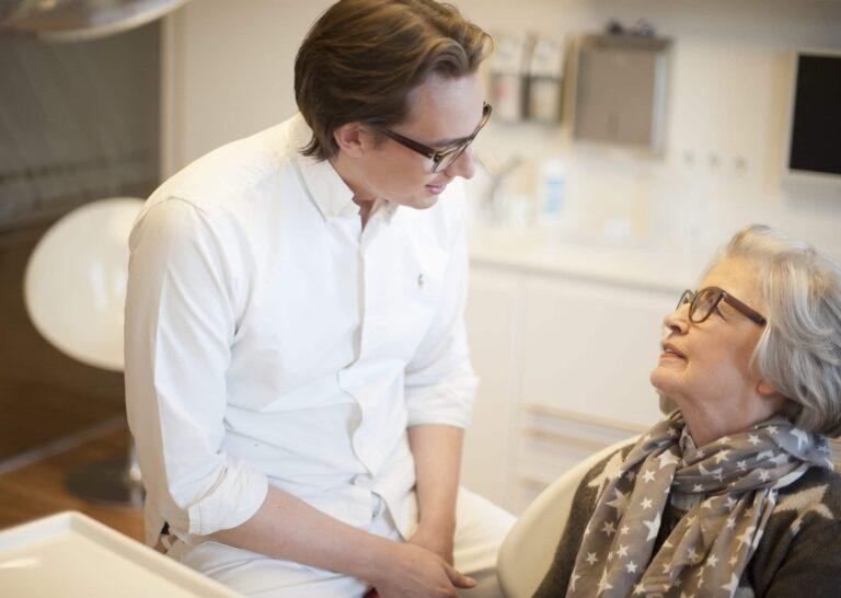 Dr. Schlotmann unterhält sich im Behandlungszimmer mit einer Patientin über die Behandlungsmethode der festen Zähne an einem Tag mit Sofortimplantaten.