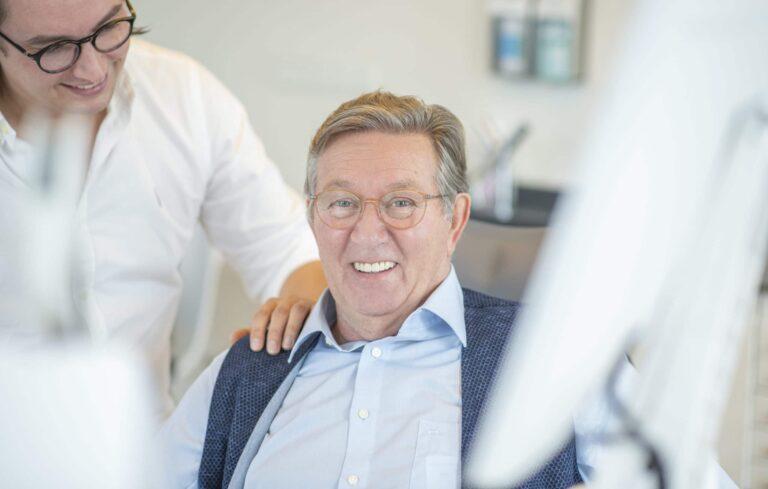 Luca Schlotmann fasst Patient Willi Kuhlmann vertrauensvoll auf die Schulter nach Behandlung