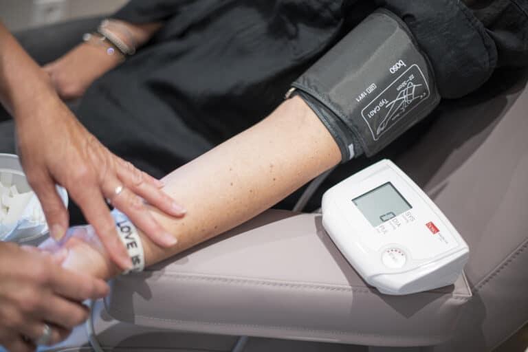 Durchführung einer Blutdruckmessung am Arm eines Patienten