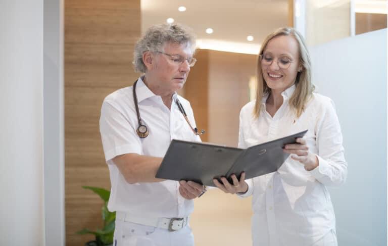 Zwei Kollegen unterhalten sich über die Inhalte einer Patientenakte
